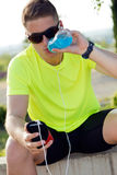 Handsome young man drinking after running. Royalty Free Stock Images