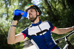 Handsome young man drinking water after cycling in the mountain. Stock Photography