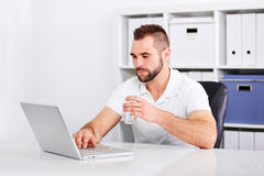 Handsome young man drinking water from a glass. Of in the office royalty free stock photos
