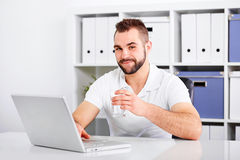 Handsome young man drinking water from a glass. Of in the office stock images