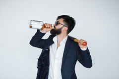 Handsome young man drinking from whiskey bottle royalty free stock image