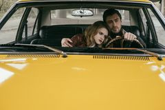 Handsome young man driving car and embracing beautiful pensive girlfriend. Handsome young men driving car and embracing beautiful pensive girlfriend royalty free stock photos