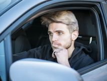 Handsome Young Man Driving a Car. Handsome Blond Young Man Driving a Car, Wearing Black Sweater. hand on wheel Royalty Free Stock Photography