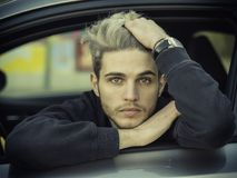 Handsome Young Man Driving a Car. Handsome Blond Young Man Driving a Car, Wearing Black Sweater. hand on wheel Royalty Free Stock Image