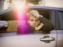 Handsome Young Man Driving a Car. Handsome Blond Young Man Driving a Car, Wearing Black Sweater. hand on wheel Stock Photography