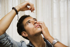 Handsome young man dropping medicine in his eye. With eye-dropper Stock Photos