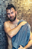 Handsome young man drying himself. Handsome bearded young man drying himself with a towel after enjoying a shower in the bathroom, upper body smiling at the Royalty Free Stock Photography