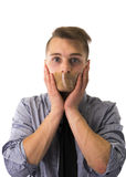 Handsome young man with duct tape on mouth cannot speak Royalty Free Stock Photo
