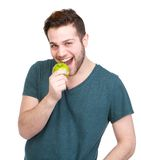 Handsome young man eating green apple Stock Photos