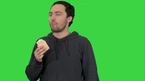 Handsome young man eating ice-cream on a green screen, chroma key stock footage