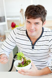 Handsome young man eating a salad in the kitchen Stock Photos