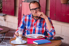 Handsome young man eating sandwich and drinking cappuccino in restaurant. Royalty Free Stock Photos
