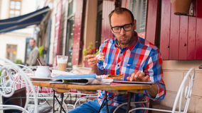 Handsome young man eating sandwich in restaurant. Stock Photo