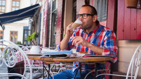 Handsome young man eating sandwich in restaurant. Royalty Free Stock Images