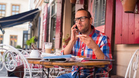 Handsome young man eating sandwich in restaurant.  He is holding a phone. Stock Photo