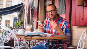 Handsome young man eating sandwich in restaurant.  He is holding a phone. Stock Photography