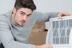 Handsome young man electrician installing air conditioning in client house. Handsome royalty free stock images