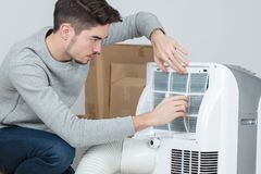 Handsome young man electrician installing air conditioning in client house. Handsome royalty free stock photo