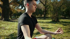 Handsome young man is engaged in meditation in lotus position. Man is dressed in black t-shirt and red shorts, sitting