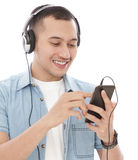 Handsome young man enjoy listening music on mobilephone with hea. Close up portrait of handsome young man enjoy listening music on mobilephone with headphones Stock Photography