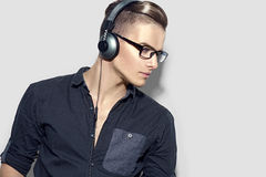 Handsome young man enjoying music on headphones Stock Image
