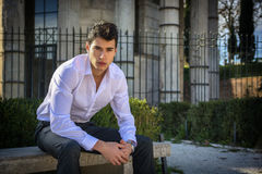 Handsome young man in European city, sitting on stone bench Royalty Free Stock Photo
