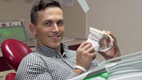 Handsome young man examining dental mold, smiling to the camera royalty free stock photos