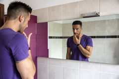 Handsome young man examining his stubble in mirror Stock Photography