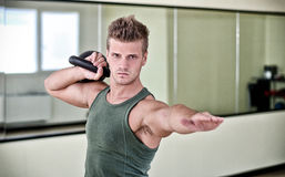 Handsome young man exercising with kettlebell in gym Stock Images