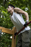 Handsome young man exercising in outdoor gym in park Royalty Free Stock Photos