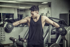 Handsome young man exercising shoulders in gym Stock Images