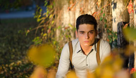 Handsome young man  in fall (autumn) near fence. Attractive young male model outdoors in nature, fall setting Royalty Free Stock Photography