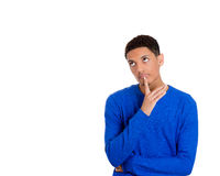 A handsome young man with finger on chin looking up and wondering what to do Stock Photo