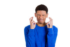 Handsome young man with fingers crossed, eyes closed, hoping for the best Royalty Free Stock Photos