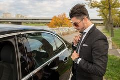 Handsome young man fixing his tie. In front of his car Stock Photography
