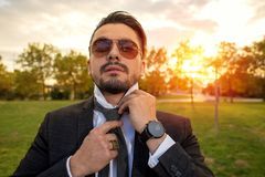 Handsome young man fixing his tie. At sunset Stock Photo