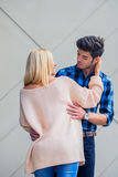 Handsome young man flirting with a sexy blonde woman on backgrou Stock Photos