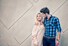Handsome young man flirting with a sexy blonde woman on cream ba. Handsome men with a blue shirt flirting with a sexy blonde women on cream background Royalty Free Stock Images
