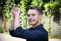 Handsome young man with flower in mouth clapping Stock Images