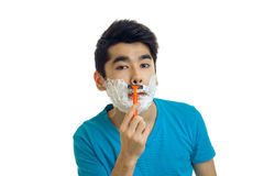 Of a handsome young man with foam on his face shaves his beard and looks into a camera Stock Photo