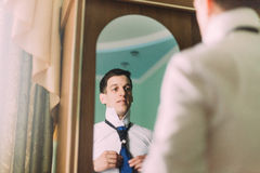 Handsome young man in formalwear adjusting his necktie and smiling while standing against mirror in hotel room Stock Image