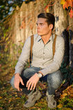 Handsome young man in front of wood fence Stock Images
