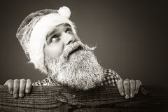 Handsome young man with frozen beard and santa cap looking up Stock Photo
