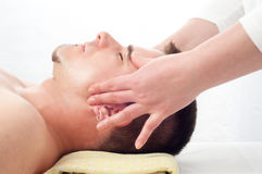 Handsome young man getting a face massage Royalty Free Stock Photos