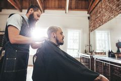 Handsome young man getting haircut stock photos