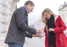 Handsome Young Man Giving His Girlfriend a Gift Box While Standing Royalty Free Stock Images