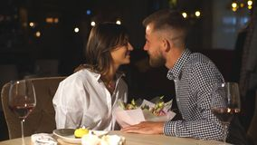 Happy romantic couple in cafe. Young man is presenting flowers to his beloved. stock footage