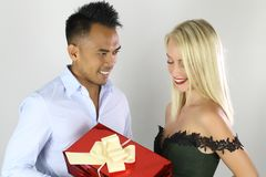 Handsome young man is giving a present to his lovely girlfriend. Handsome young men is giving a present to his lovely girlfriend on a white background Royalty Free Stock Photo