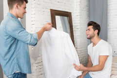 Handsome young man giving a shirt to his boyfriend. Choosing a shirt. Handsome happy young men smiling and giving a shirt to his boyfriend while standing in Stock Photo