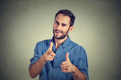 Handsome young man giving thumbs up pointing fingers at camera, picking you. Portrait handsome young smiling man giving thumbs up pointing fingers at camera Stock Image